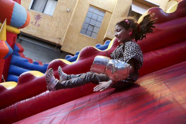 Nour, a 9 year-old girl, who lives in the rebel-held neighborhood of Jobar in Damascus, plays on an inflatable slide in the neighboring suburb of Hamouriyeh, where they came to celebrate the Muslim holiday of Eid al-Fitr, which marks the end of the holy month of Ramadan, Syria July 18, 2015. (Photo by Bassam Khabieh/Reuters)