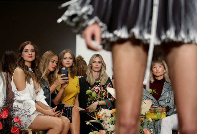 Members of the audience sit in the centre of the catwalk as the watch models for the C/MEO Collective walk by at Fashion Week Australia in Sydney on May 17, 2017. (Photo by Jason Reed/Reuters)