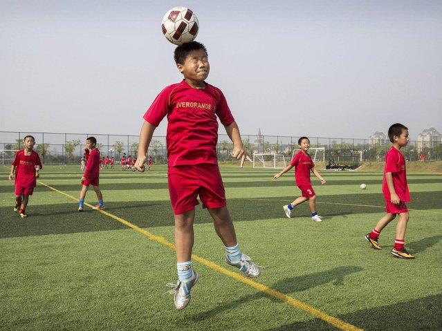 A young Chinese football player leaps up to head the ball during training at the Evergrande International Football School near Qingyuan in Guangdong Province. (Photo by Kevin Frayer/Getty Images)