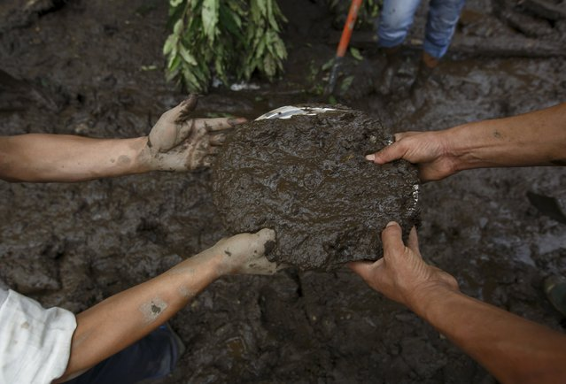 A plate is used to dig out mud while searching for landslide victims at Lumle village in Kaski district July 30, 2015. (Photo by Navesh Chitrakar/Reuters)