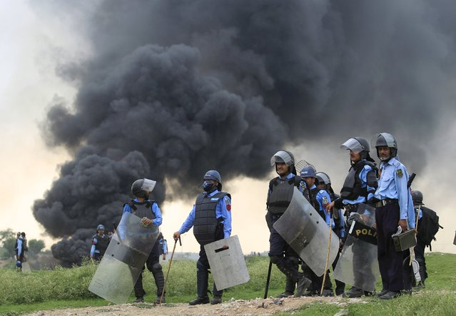 Policemen stand as smoke billows into the sky during clashes with residents of an illegal settlement on the outskirts of Islamabad July 30, 2015. (Photo by Faisal Mahmood/Reuters)