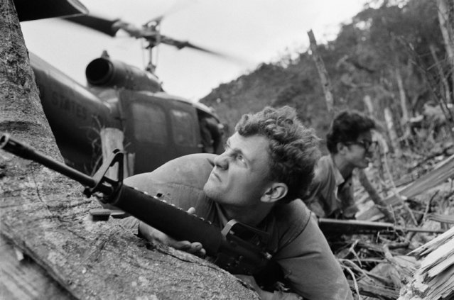 A U.S. GI grimaces as down blast from a helicopter in background kicks up dust around his face. He was part of a detail of men from Charlie Company of the 101st airborne protecting a landing zone for the chopper that served as a resupply link for the men, who were probing a North Vietnamese staging area, May 25, 1971. (Photo by AP Photo)
