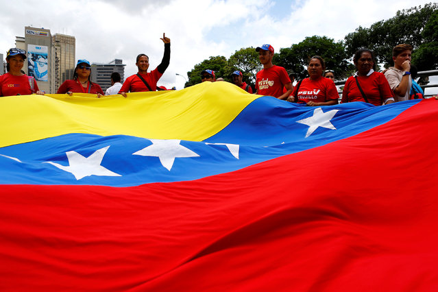 Pro-government supporters hold a Venezuelan flag during a rally of members of the education sector in Caracas, Venezuela June 14, 2016. (Photo by Ivan Alvarado/Reuters)