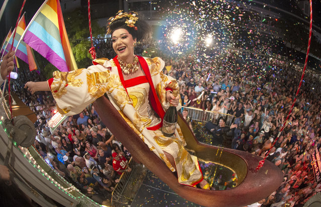 """In this photo provided by the Florida Keys News Bureau, female impersonator Gary Marion, known as """"Sushi"""", sits in a large replica of a women's high-heel shoe while dangling above Duval Street, late Tuesday, December 31, 2019, in Key West, Fla. The Red Shoe Drop is one of six offbeat Key West warm-weather takeoffs on New York City's Times Square """"ball drop"""" set to celebrate the beginning of 2020. (Photo by Andy Newman/Florida Keys News Bureau via AP Photo)"""