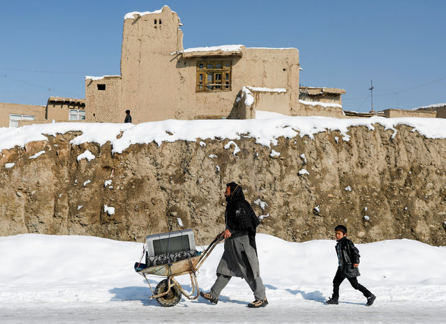 An Afghan man carries a tv on a cart in a snow-covered street in Kabul, Afghanistan on January 7, 2020. Wintry weather has led to an unofficial ceasefire in many parts of the country after weeks of violence claimed hundreds of lives. (Photo by Mohammad Ismail/Reuters)