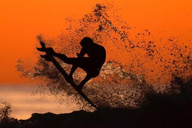 A surfer takes some air off a wave while surfing after sunset in Cardiff, California, U.S., January 7, 2020. (Photo by Mike Blake/Reuters)