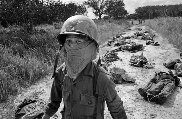 In this Nov. 27, 1965 photo, a Vietnamese litter bearer wears a face mask to keep out the smell as he passes the bodies of U.S. and Vietnamese soldiers killed in fighting against the Viet Cong at the Michelin rubber plantation, about 45 miles northeast of Saigon
