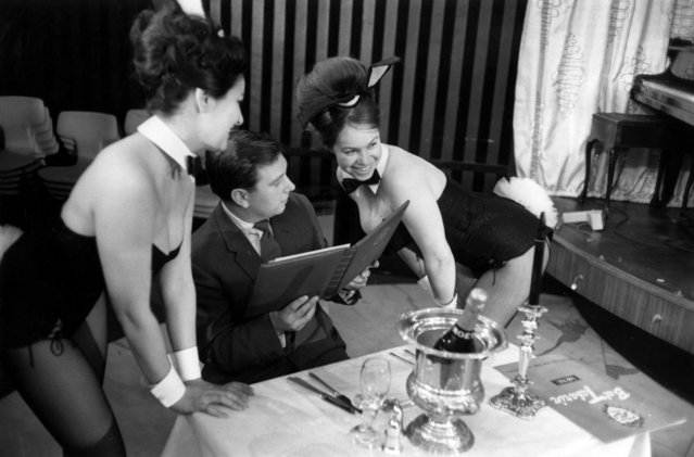 "Playboy-style ""bunny girls"" serving a customer with a champagne lunch at Paul Raymond's Bal Tabarin nightclub in Hanover Square, London, 11th February 1963. (Photo by Victor Blackman/Daily Express/Hulton Archive/Getty Images)"