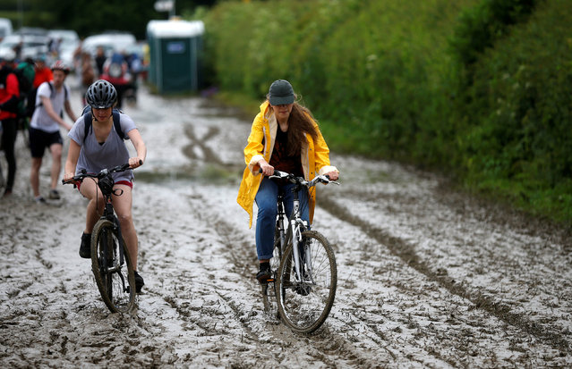 Revellers ride their bikes on a muddy road as they arrive at Worthy Farm in Somerset for the Glastonbury Festival, Britain June 22, 2016. (Photo by Stoyan Nenov/Reuters)