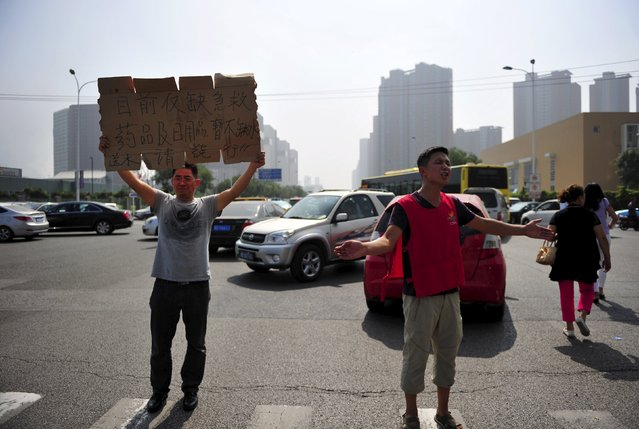 """Volunteers guide the traffic on a street near the playground of a primary school, which serves as a temporary shelter for victims, after explosions at Binhai new district in Tianjin, China, August 13, 2015. The placard reads: """"Currently lack of first-aid medicine and daily necessities, water is abundant, people who are coming to give water please go around"""". (Photo by Reuters/Stringer)"""