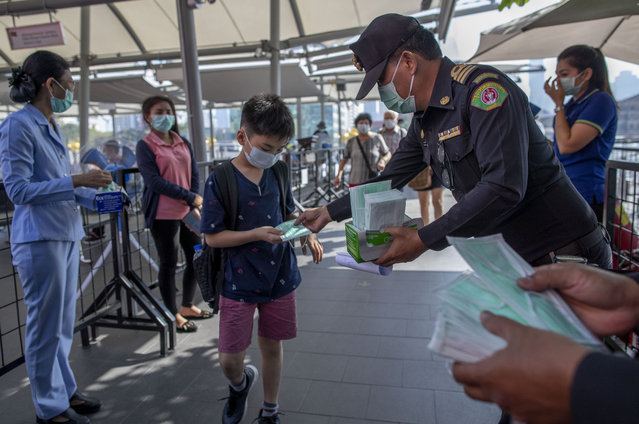 Health officials distribute protective face masks for visitors at a luxury mall in Bangkok, Thailand, Tuesday, January 28, 2020. Panic and pollution drive the market for protective face masks, so business is booming in Asia, where fear of the coronavirus from China is straining supplies and helping make mask-wearing the new normal. (Photo by Gemunu Amarasinghe/AP Photo)