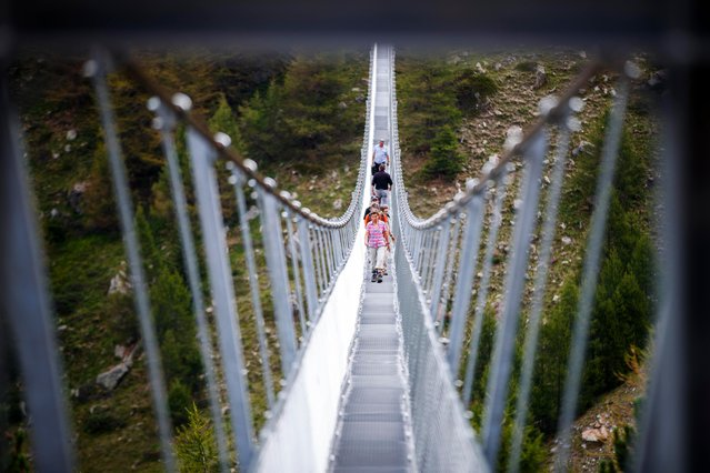 """People walk on the """"Europabruecke"""", supposed to be the world's longest pedestrian suspension bridge with a length of 494m, after the official inauguration of the construction in Randa, Switzerland, on Saturday, July 29, 2017. The bridge is situated on the Europaweg that connects the villages of Zermatt and Graechen. (Photo by Valentin Flauraud/Keystone via AP Photo)"""