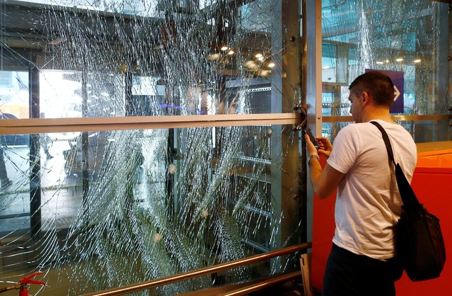 A man takes pictures of a broken window at Turkey's largest airport, Istanbul Ataturk, Turkey, following yesterday's blasts June 29, 2016. (Photo by Osman Orsal/Reuters)