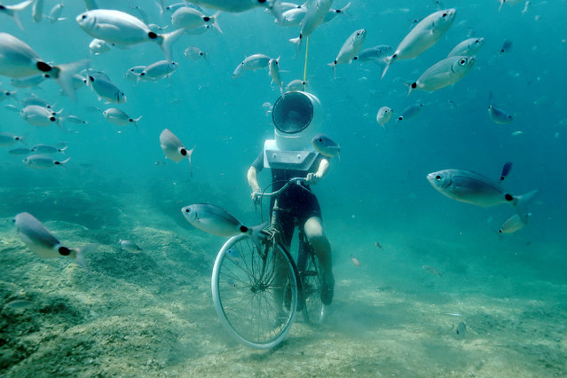A woman dives and pretends to ride a bike in Underwater Park in Pula, Croatia, August 1, 2017. (Photo by Antonio Bronic/Reuters)