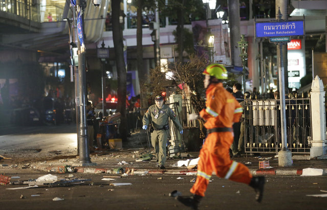 Emergency personnel work at the scene after an explosion in Bangkok, Monday, August 17, 2015. A large explosion rocked a central Bangkok intersection during the evening rush hour, killing a number of people and injuring others, police said. (Photo by Sackchai Lalit/AP Photo)