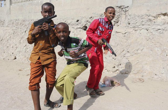 Somali boys play with their toy guns after attending Eid al-Fitr prayers to mark the end of the fasting month of Ramadan in Somalia's capital Mogadishu, July 28, 2014. (Photo by Feisal Omar/Reuters)