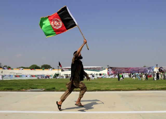 An Afghan man holds an Afghanistan national flag during a ceremony marking the country's 96th Independence Day in Jalalabad province, Afghanistan August 19, 2015. (Photo by Reuters/Parwiz)