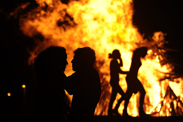People attend a party held during the night of the San Juan bonfire on the beach of Playa de Poniente in Gijon early June 24, 2014. Fires formed by burning unwanted furniture, old school books, wood and effigies of malign spirits are seen across Spain as people celebrate the night of San Juan, a purification ceremony coinciding with the summer solstice. (Photo by Eloy Alonso/Reuters)