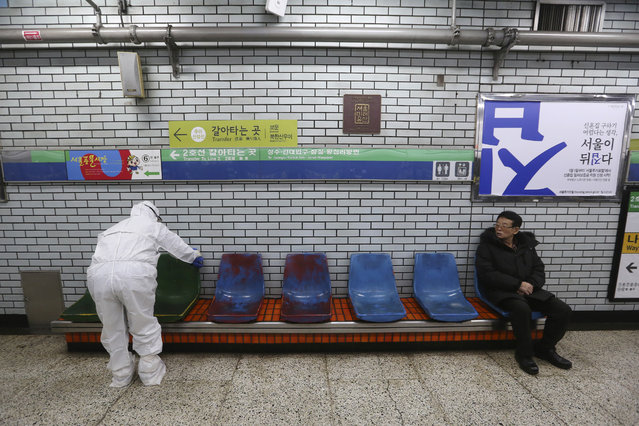 A worker wearing protective gears disinfect chairs as a precaution against the coronavirus at a subway station in Seoul, South Korea, Friday, February 21, 2020. (Photo by Ahn Young-joon/AP Photo)