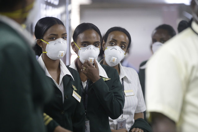Ethiopian Airline cabin crew wait to be screened by Nigerian port health officials for COVID-19 virus, upon arrival at the Murtala Muhammed International Airport in Lagos, Nigeria, Wednesday, March 4, 2020. (Photo by Sunday Alamba/AP Photo)