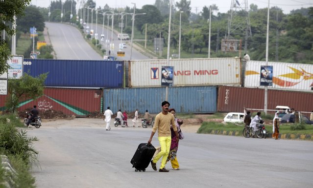 A couple walks on a major highway in front of containers placed to block roads in Islamabad August 13, 2014. Thousands of riot police sealed off Pakistan's capital with barbed wire and shipping containers on the eve of the country's Independence Day, in a bid to foil mass protests aimed at toppling embattled Prime Minister Nawaz Sharif. (Photo by Faisal Mahmood/Reuters)
