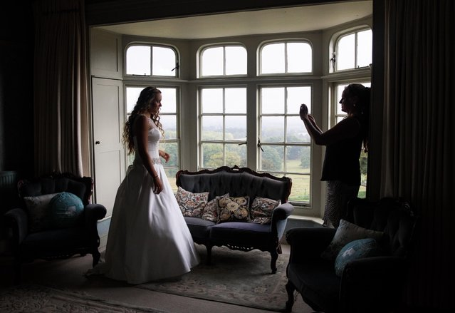 Former debutante Charlotte Wotner, 48 (R) takes a picture of her daughter debutante Eliza Lewis, 17, (L) at Boughton Monchelsea Place ahead of the Queen Charlotte's Ball on September 9, 2017 in Maidstone, England. (Photo by Jack Taylor/Getty Images)
