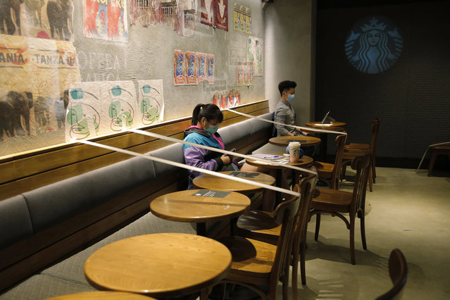 Tables and chairs are taped for the social distancing law enforcement to help curb the spread of the coronavirus at a Starbucks coffee shop in Hong Kong, Sunday, March 29, 2020. (Photo by Kin Cheung/AP Photo)