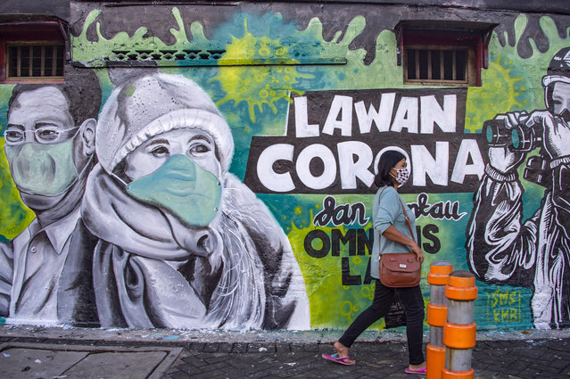 An Indonesian woman walks past a mural that invite people to fight against the COVID-19 coronavirus in Surabaya, East Java on March 26, 2020. (Photo by Juni Kriswanto/AFP Photo)