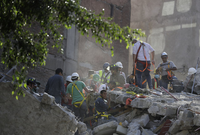 A man calls for a gas mask as rescue workers search for people trapped in the rubble of a collapsed building in the Condesa neighborhood of Mexico City, Tuesday, September 19, 2017. (Photo by Rebecca Blackwell/AP Photo)