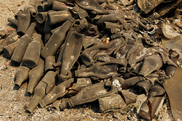 A pile of melted bottles lay on the ground at the site of a destroyed home after the Soberanes Fire burned through the Palo Colorado area, north of Big Sur, California, July 31, 2016. (Photo by Michael Fiala/Reuters)