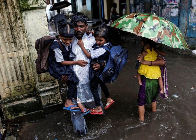 A man carries schoolchildren through a flooded street during monsoon rains in Mumbai, India, August 1, 2016. (Photo by Danish Siddiqui/Reuters)