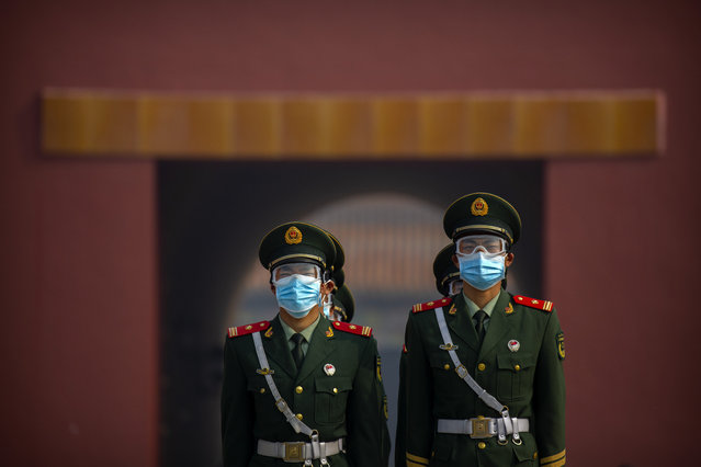 Chinese paramilitary police wear face masks to protect against the spread of the new coronavirus as they stand in formation outside an entrance to the Forbidden City in Beijing, Friday, May 1, 2020. (Photo by Mark Schiefelbein/AP Photo)