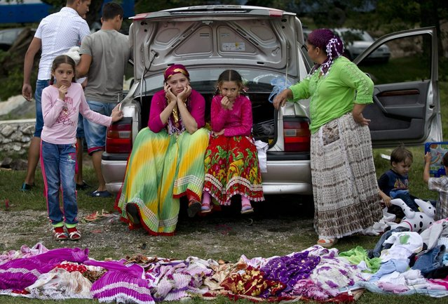 A Roma family waits for customers for traditional skirts as the Roma community celebrates the Birth of the Virgin Mary in Costesti, Romania, Monday, September 8, 2014. Thousands of Gypsies or Roma gather on a hillside after attending a religious service in a nearby monastery and celebrate the religious holiday by sharing food and playing traditional music until the next dawn. (Photo by Vadim Ghirda/AP Photo)