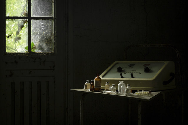 Bottles of chemicals and syringes in a shadowy room. (Photo by Thomas Windisch/Caters News)