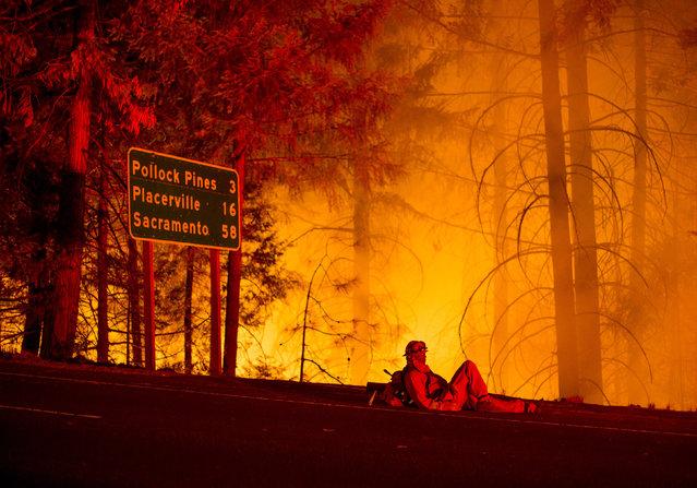 A firefighter battling the King Fire watches a backfire burn along Highway 50 in Fresh Pond, California September 16, 2014. (Photo by Noah Berger/Reuters)
