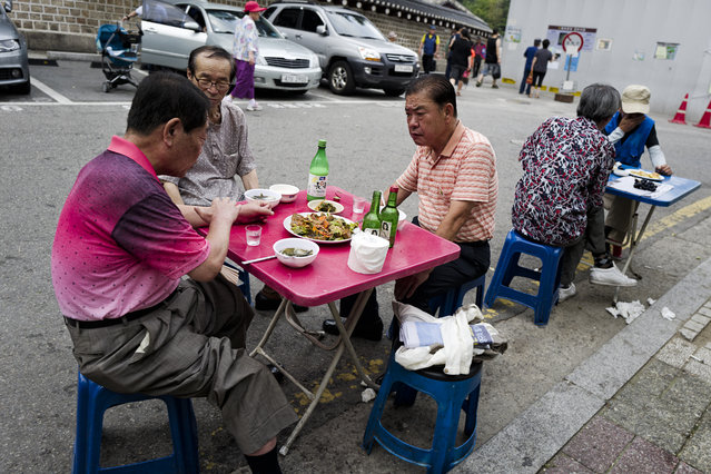 People have chats drinking soju (Korean gin) and makgeolli (Korean rice wine) at open tables by restaurants on a street at Jongno-gu on August 1, 2015 in Seoul, South Korea. (Photo by Shin Woong-jae/The Washington Post)
