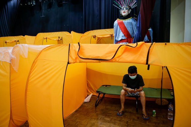 A man being monitored for COVID-19 disease symptoms looks at his mobile phone inside an isolation tent at a performing arts theater that was converted into a quarantine facility for people showing symptoms of the COVID-19 disease in Jakarta, Indonesia, 19 May 2020. Countries around the world are taking increased measures to stem the spread of the SARS-CoV-2 coronavirus which causes the COVID-19 disease. (Photo by Mast Irham/EPA/EFE/Rex Features/Shutterstock)