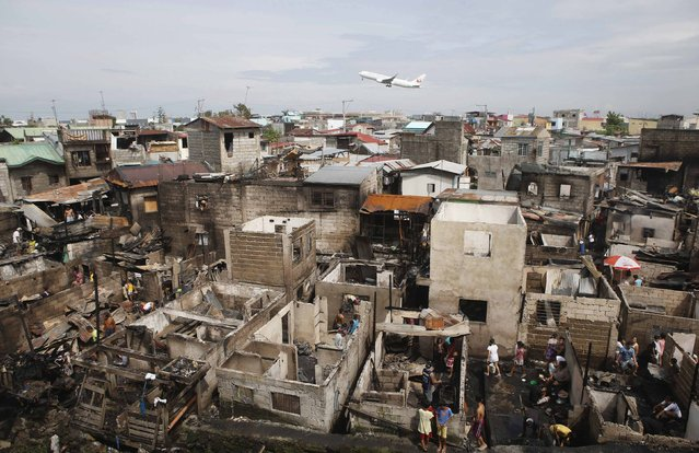 Residents sift through the ruins of their homes, which were razed by a neighbourhood fire as an aircraft takes off at the nearby Ninoy Aquino International airport in Paranaque, Metro Manila September 16, 2014. Some 100 families were left homeless after 60 houses in the neighbourhood of Paranaque were destroyed by a fire caused by faulty electrical wiring on Monday evening, local media said. (Photo by Erik De Castro/Reuters)
