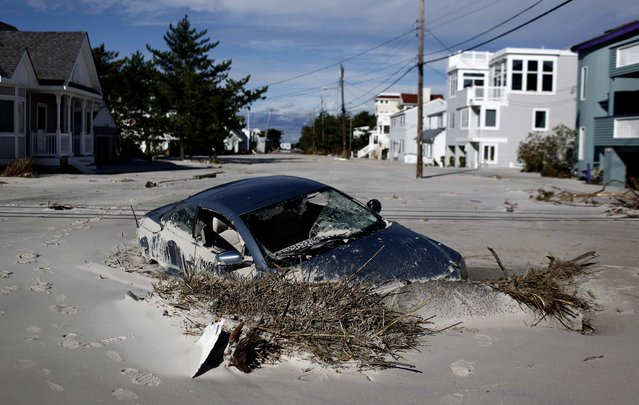 A car is submerged in sand on the south end of Long Beach Island, N.J. in the aftermath of superstorm Sandy, October 31, 2012.  (Photo by Luke Sharrett/The New York Times)