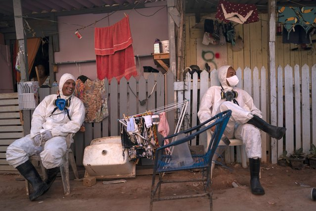 "Welington Goncalves, right, sits next to his colleague as they wait to refill their tanks during a disinfection to help contain the spread of the new coronavirus in an area occupied by squatters in a poor region of Rio de Janeiro, Brazil, Friday, June 26, 2020. For the 21-year-old volunteer, who lives in this occupation, the sanitization is a way to avoid the COVID-19 and if it was not for him and other volunteers working on it, ""the situation would be worse"". (Photo by Leo Correa/AP Photo)"