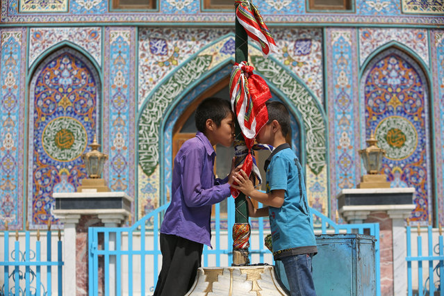 In this September 11, 2017 file photo, Afghan Shiite boys kiss a holy mace to bring blessings, at the Karti Sakhi shrine, in Kabul, Afghanistan. (Photo by Rahmat Gul/AP Photos)
