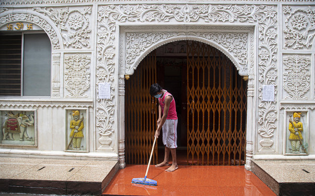 An Indian boy cleans the entrance area of a temple during the reimposed lockdown in Gauhati, India, Monday, June 29, 2020. India has reported a new daily record of nearly 20,000 new infections as several Indian states reimpose partial or full lockdowns to stem the spread of the coronavirus. (Photo by Anupam Nath/AP Photo)