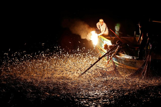 """Fishermen use a fire to attract fish on a traditional """"sulfuric fire fishing"""" boat in New Taipei City, Taiwan June 19, 2016. (Photo by Tyrone Siu/Reuters)"""