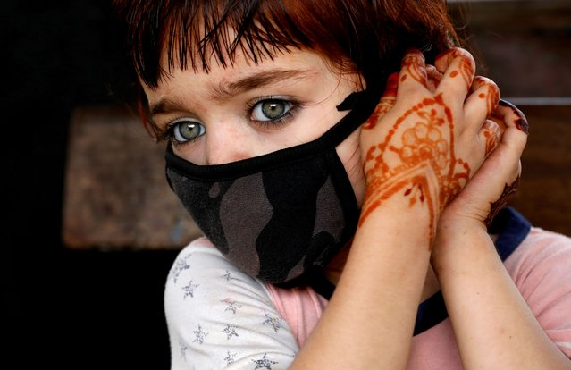 4-year-old Tasmina adjusts her protective face mask as she waits with her family for a train at a railway station, as the outbreak of the coronavirus disease (COVID-19) continues, in Karachi, Pakistan on June 9, 2020. (Photo by Akhtar Soomro/Reuters)