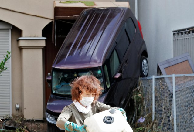 Debris is cleared from a house as an overturned car is seen after floods caused by torrential rain in Hitoyoshi town, Kumamoto Prefecture, southwestern Japan, July 8, 2020. (Photo by Kim Kyung-Hoon/Reuters)