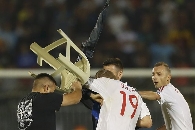 A fan of Serbia scuffles with Bekim Balaj (C) of Albania next to his teammate Ansi Agolli (R) and Nenad Tomovic of Serbia during their Euro 2016 Group I qualifying soccer match at the FK Partizan stadium in Belgrade October 14, 2014. (Photo by Marko Djurica/Reuters)