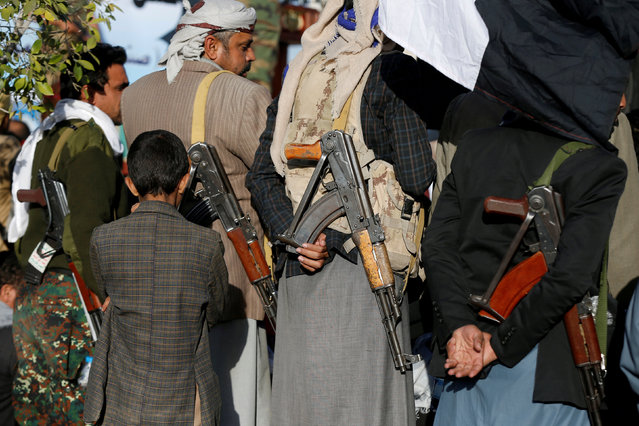 A boy stands behind armed Houthi followers attending a rally to celebrate the killing of Yemen's former president Ali Abdullah Saleh in Sanaa, Yemen December 5, 2017. (Photo by Khaled Abdullah/Reuters)