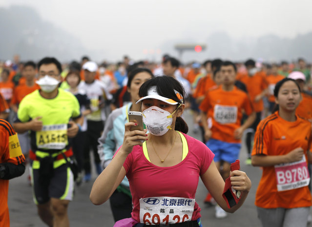 A runner, wearing a mask to protect herself from pollutants, looks at her smartphone as she and others jog past Chang'an Avenue near Tiananmen Square shrouded in haze at the start of 2014 Beijing International Marathon in Beijing, China Sunday, October 19, 2014. (Photo by Andy Wong/AP Photo)