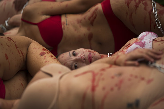 Animal rights activist, stained with fake blood, perform during a protest against the use of animal skins in the clothes and fashion industry, in Madrid, Sunday, December 10, 2017. (Photo by Francisco Seco/AP Photo)