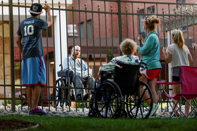 Family and friends of Myron Wagner, 82, visit him from outside Bethany Retirement Living, as they practice social distancing amid the spread of the coronavirus disease (COVID-19), in Fargo, North Dakota, U.S. July 15, 2020. (Photo by Dan Koeck/Reuters)
